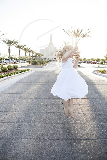 Jumping twirling girl in white dress. photo