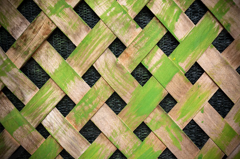 Part of an old green painted wooden fence closeup view.  photo