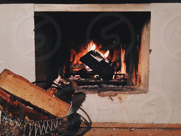 fire in a fireplace with wood in a metal basket photo