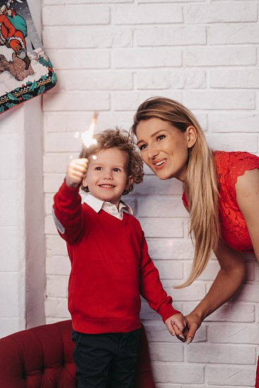 Son sits on his mother's shoulders in Christmas decorated studio photo