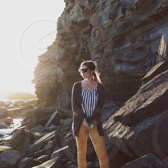 woman standing near the rock with yellow jeans photo