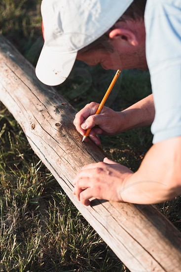Man making mark by  using pencil after measuring of timber while working in garden photo