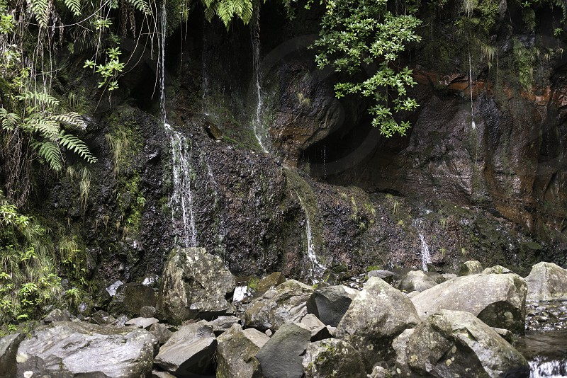waterfall on madeira island on levada das 25 fontes tracking in wild nature with red rocks and stones photo