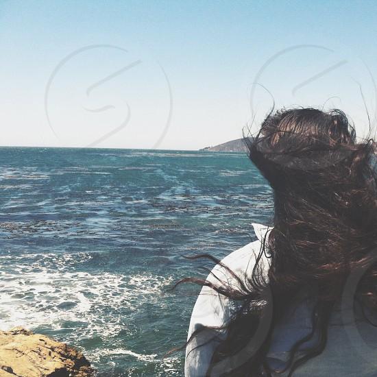 Dark long hair blowing in the ocean breeze photo