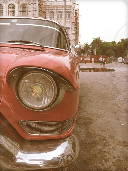 red vintage car on gray sand during daytime photo