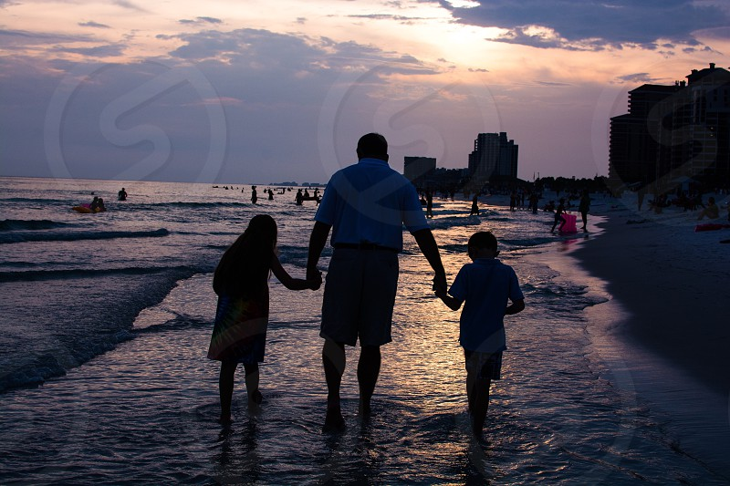 man holding children with his left and right hands walking in body of water near shore during sunset photo