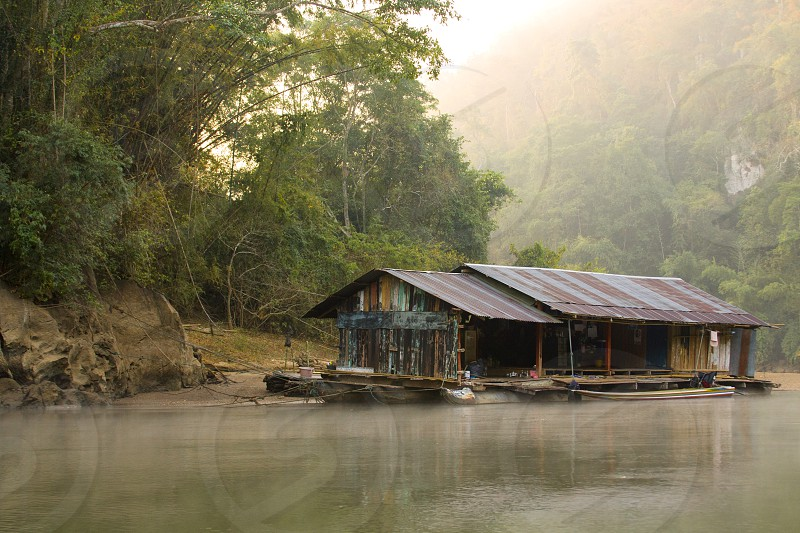 Old wooden house on the tropical river on the morning photo