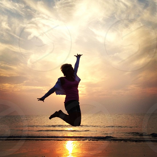 a woman wearing cardigan and tank top on the air after she jumps with her left hand lifted above and her legs are bent against beach body of water and sky full of think clouds photo
