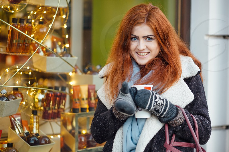 Beautiful young red hair girl standing on the street photo