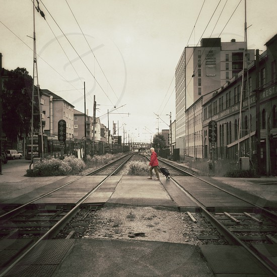 woman in red jacket and gray pants crossing on the railroad photo