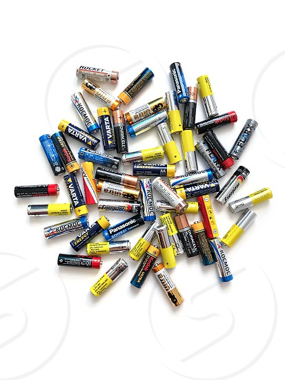 Moscow Russia - April 19 2019: Different brands of colorful batteries on white isolate background Energy source for portable technology in AA size. View directly above photo