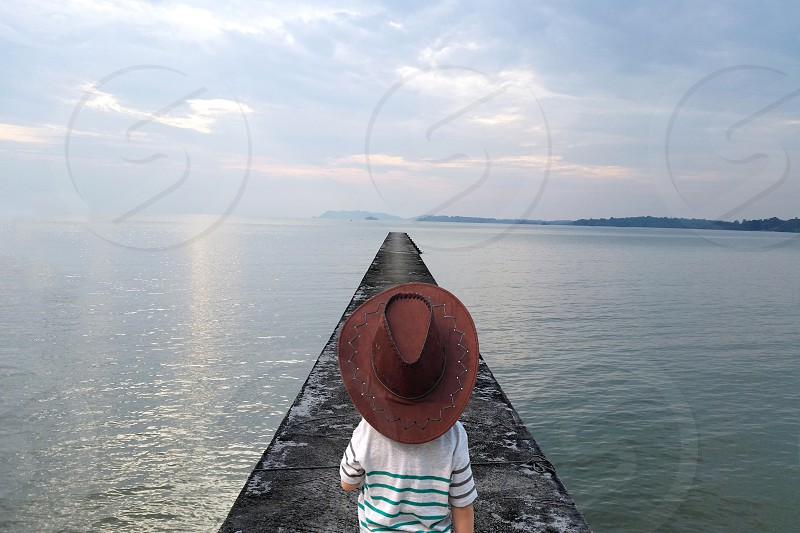 child wearing brown cowboy hat standing on gray concrete pier under white cloudy sky photo