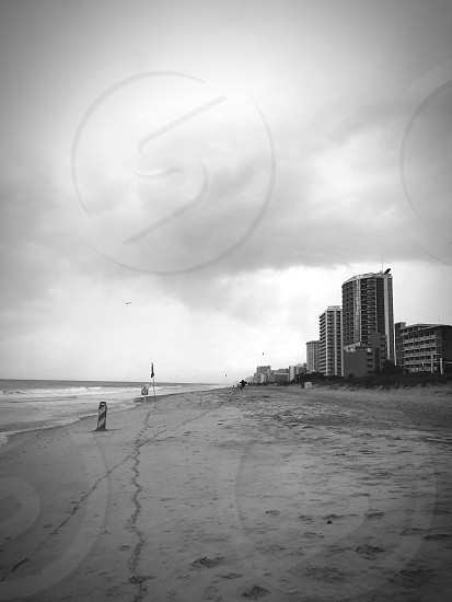 Beach sea seashore building outside exterior black and white footprint sky clouds photo