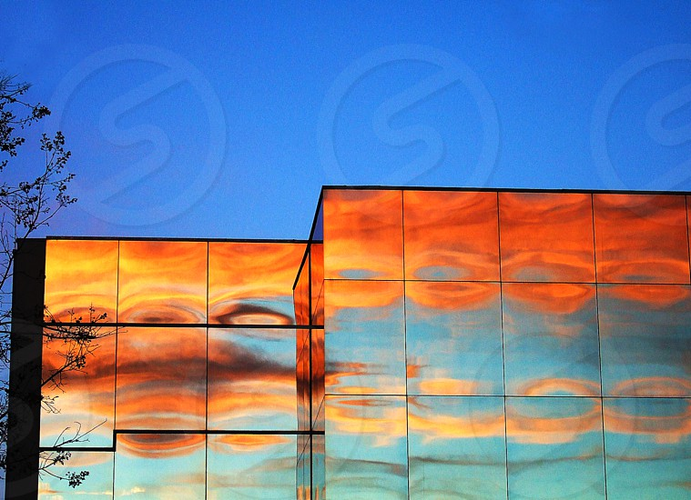 A glass building glows orange in the morning sunrise. photo