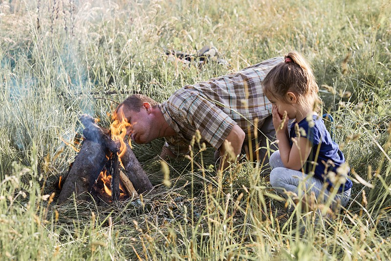Man starting a campfire blowing on a fire. Little girl sitting in a grass beside a campfire. Candid people real moments authentic situations photo