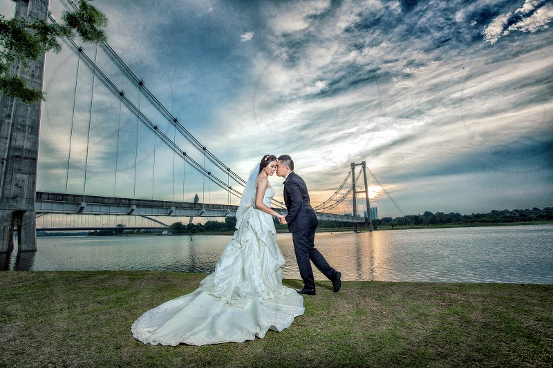 couple kissing standing on green grass with bridge background near blue body of water under white clouds and blue sky during daytime photo