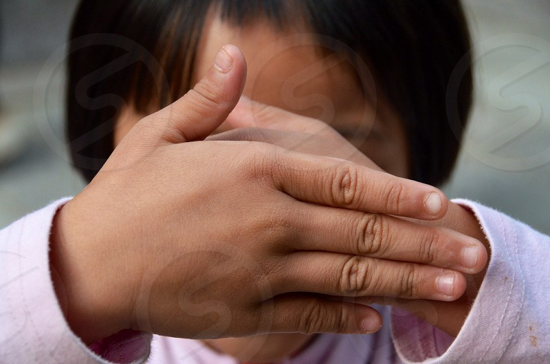 girl covering her face with her hands photo