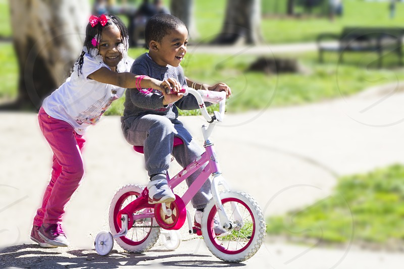 two kid's playing bike outside during daytime photo