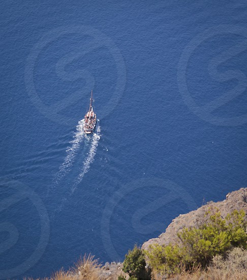 Looking down the cliff-side at a leisure boat in the Caldera in Santorini Greece. photo