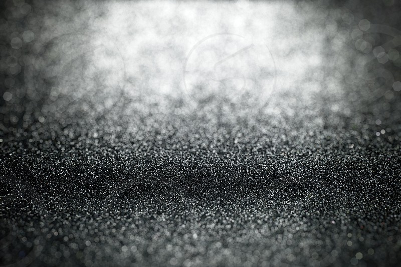 Abstract black light glitter background with selective focus on surface textures with blurred foreground and background photo
