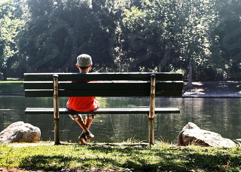 A little boy - seen from behind - sits on a bench in a park and fishes in a pond. photo