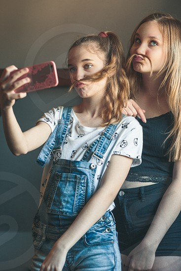 Young women taking selfie using smartphone camera. Girls making faces enjoying taking funny pictures together photo