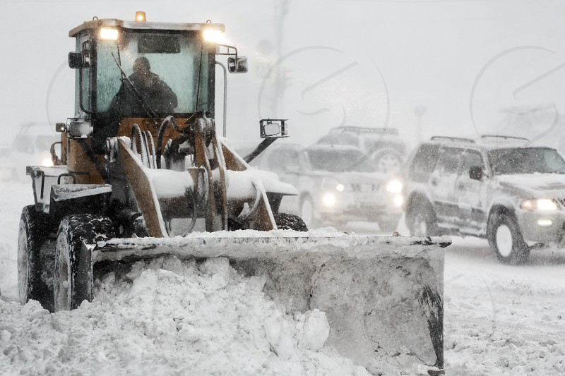 Front End Wheel Loader removes snow from road during heavy snow winter storm poor visibility. Winter highway maintenance in Petropavlovsk-Kamchatsky City. Kamchatka Peninsula Russian Far East. photo
