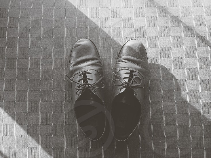 black leather shoes on a gray checkered floor photo
