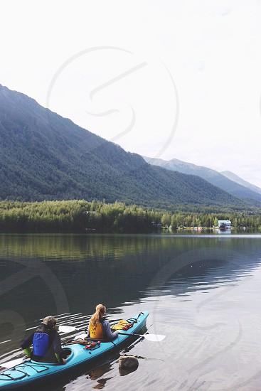 man and woman sitting on kayak boat photo