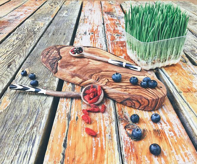 Superfoods superfood goji blueberry wheatgrass spoon wood green photo