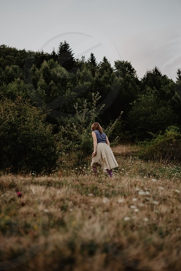 Woman from behind walking in the woods. photo