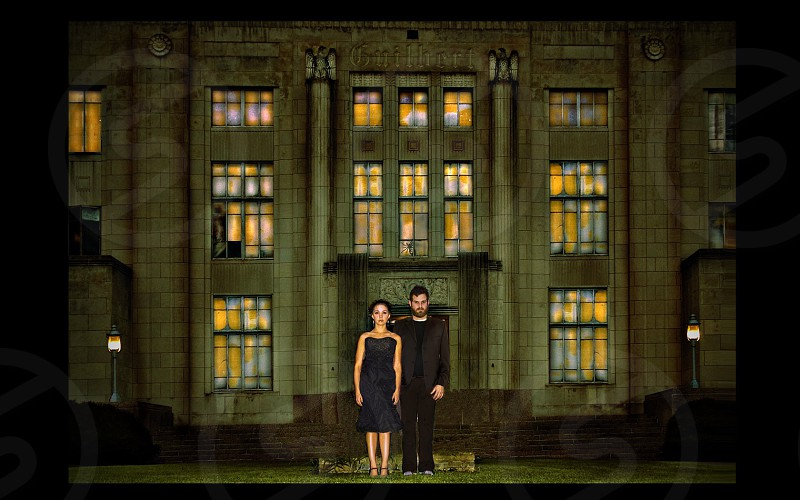 Couple wearing all black in front of historic courthouse at night.  photo