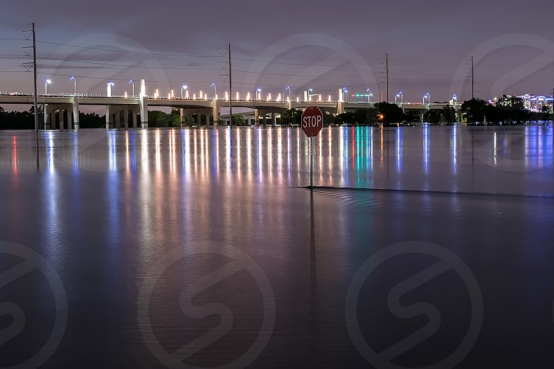Night photo of a stop sign in the flood waters of the Trinity River with the lights of the Hampton Street Bridge in Dallas Texas in the background. May 31 2015 photo