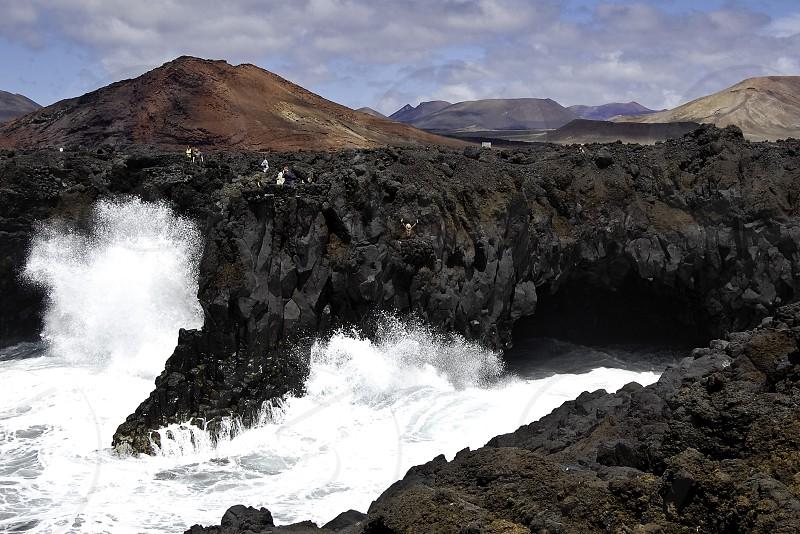 waves crashing against dark rocky cliff photo