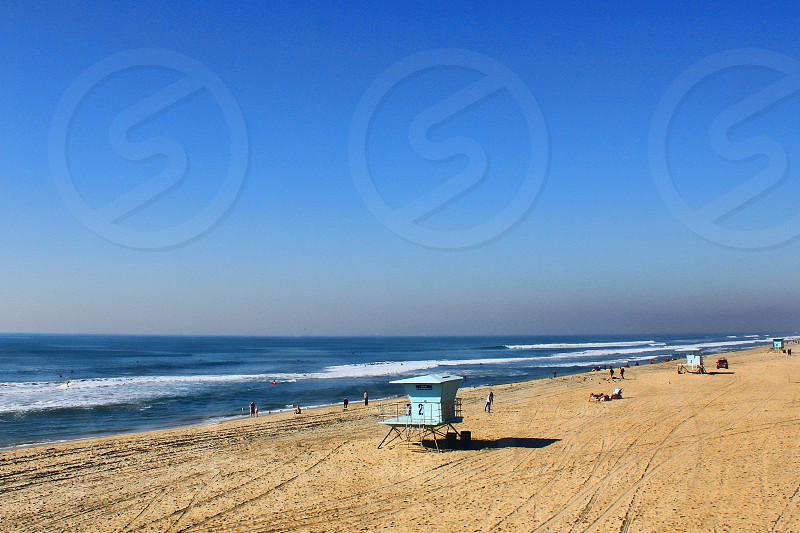 Row of Life guard huts seen from a distance along a sandy beach photo