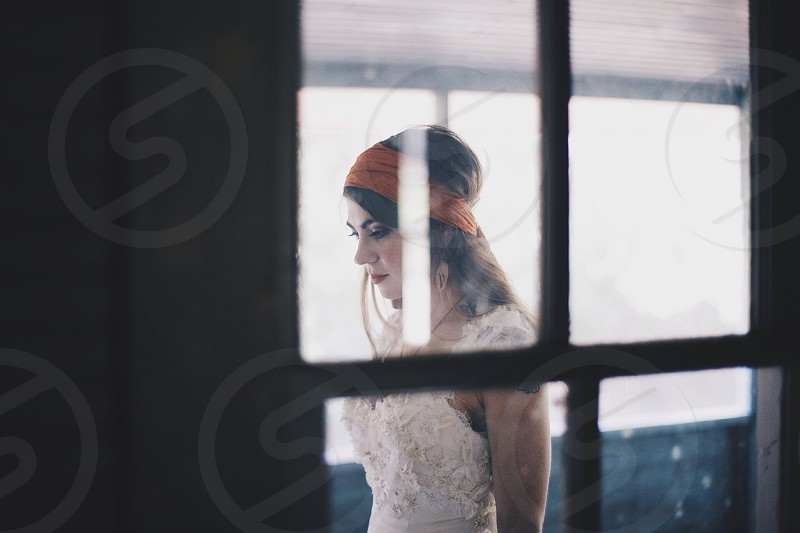 woman in white lace dress and orange fabric headband photo