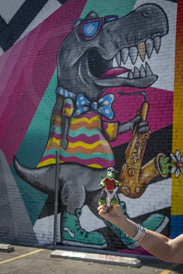 Woman off camera holding toy dinosaur in front of mural depicting dinosaur playing music photo