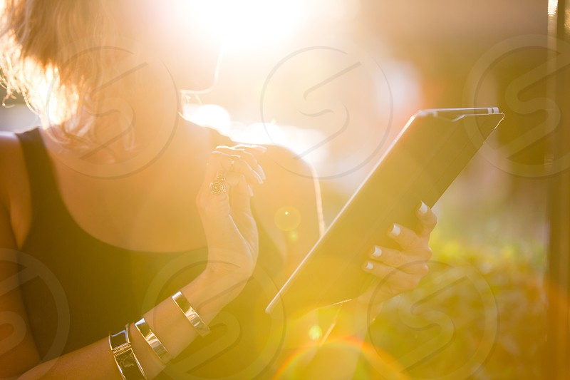 Beautiful Woman on digital pad with sunflare photo