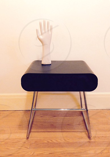 Glove mold rests on a mid-century end table. photo