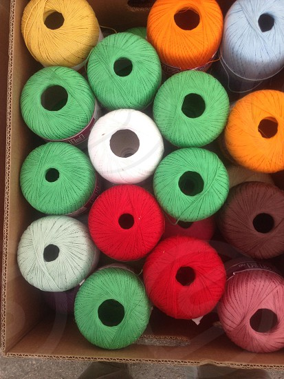 white green red orange brown pink and blue thread spools photo