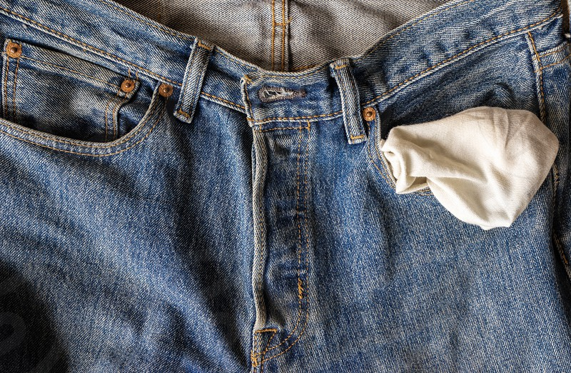 close up jeans front pocket  turning out the empty pockets with no money on wooden ground texture background with copy space photo