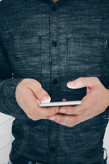 young dressed casually man typing on a smartphone photo