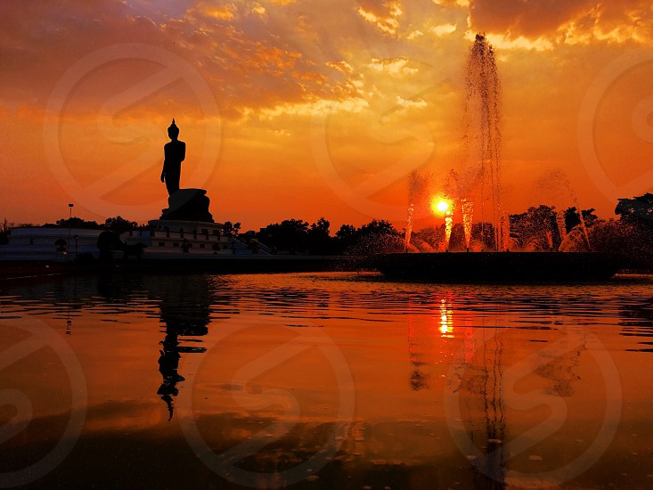 Buddha image statue monument Buddhamonthon Buddhism park outdoor sunset red orange gold silhouette shadow reflection sundown calm serenity peace silence relax pray quietness zen meditation still practice religion Thailand Bangkok photo