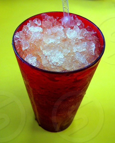 Red plastic cup filled with chipped ice in beverage with straw on yellow background photo