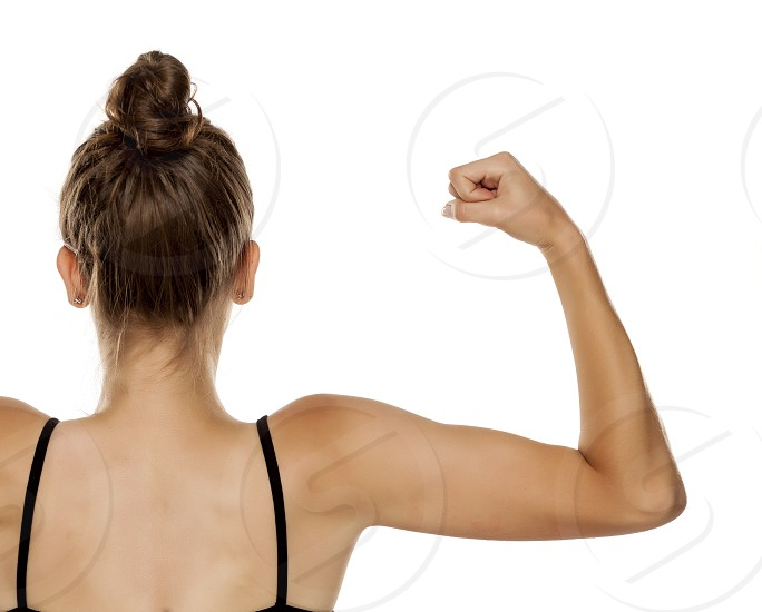 Back view of young woman showing her arms on white background photo