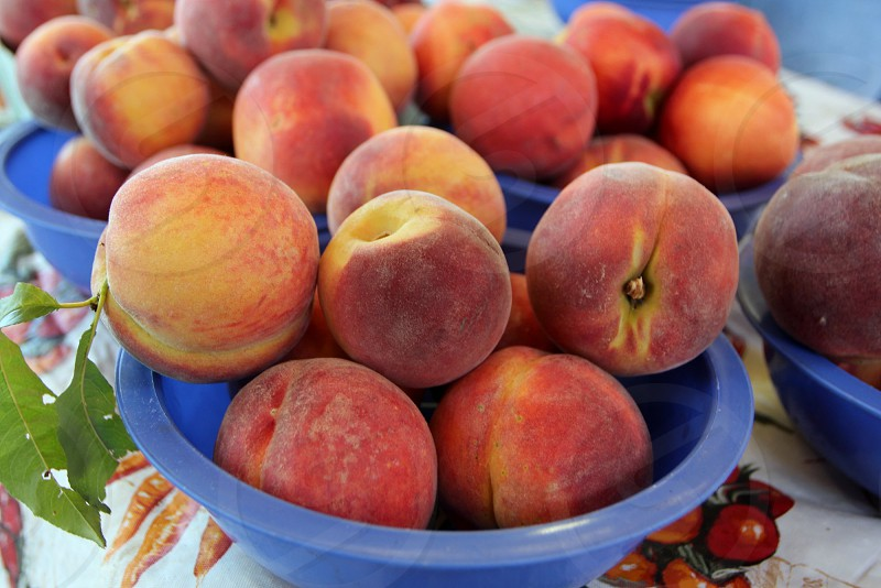 Blue bowls of peaches at farmers market photo