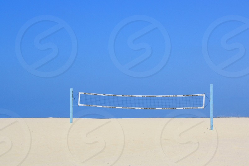 Volleyball net stands on an empty beach with white sand against a blue sky. photo