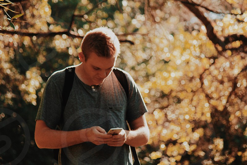 man in grey henley t-shirt using smartphone standing during daytime photo
