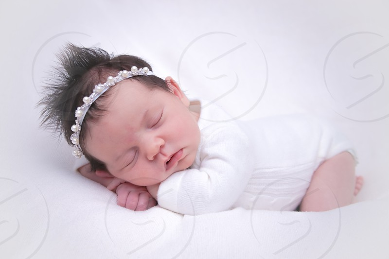 baby in white long sleeve onesie white white headband lying on belly sleeping photo