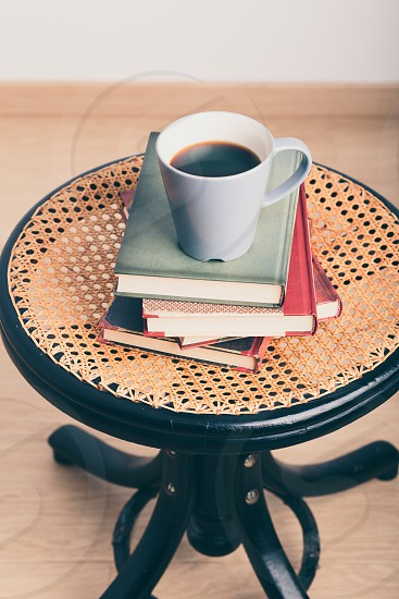 A few books with cup of coffee on chair photo